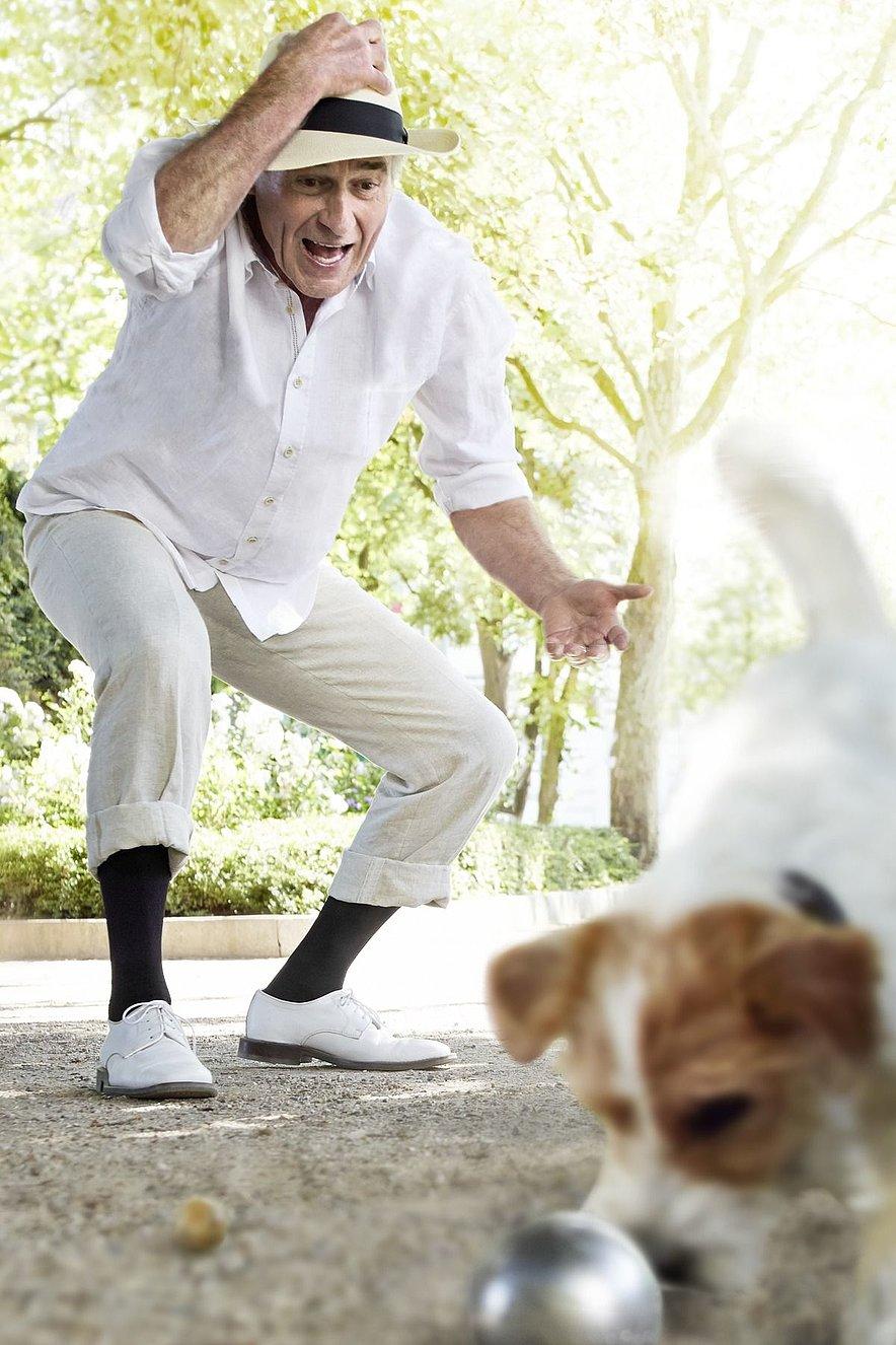 Boulespieler mit Hund draußen Spaß -