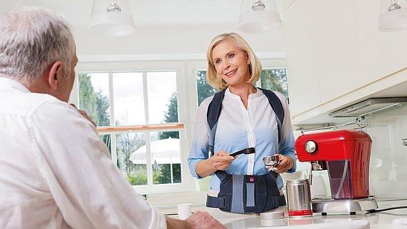 Frau trägt Spinomed und macht Kaffee -