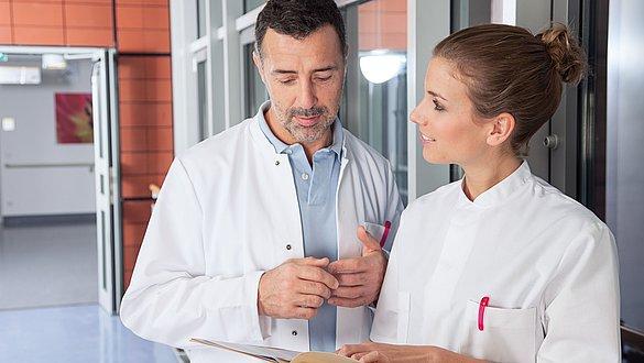 Arzt und Krankenschwester besprechen sich -