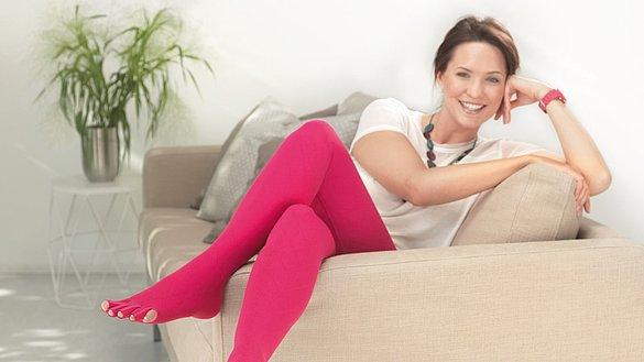 Frau entspannt mit Flachstrickversorgung auf dem Sofa -