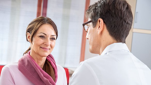 Arzt begrüßt Patientin -
