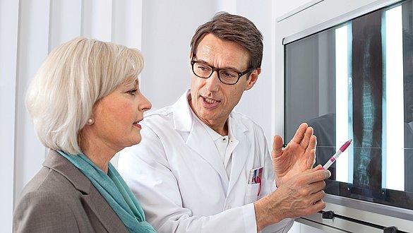 Arzt berät Patientin zu Röntgenbild