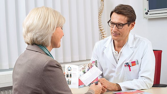 Arzt berät Patientin anhand einer Broschüre -