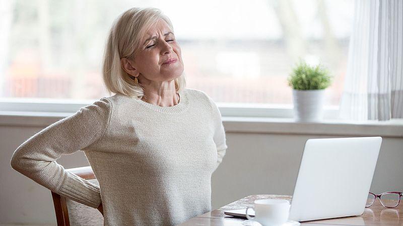 Frau mit Rückenschmerzen: Mehr zur Ursachen und Therapie